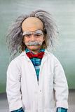 Smiling boy dressed as scientist standing against board. Portrait of smiling boy dressed as scientist standing against board in classroom Stock Images