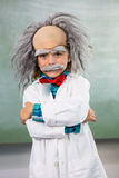 Smiling boy dressed as scientist standing with arms crossed. Portrait of smiling boy dressed as scientist standing with arms crossed in classroom Stock Image
