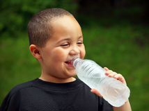 Smiling boy drinking. Smiling latino boy portrait outdoors drinking water Stock Images