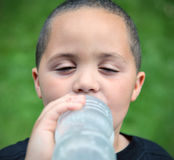 Smiling boy drinking. Smiling latino boy portrait outdoors drinking water Stock Photography