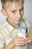 Smiling boy drinking milkshake Royalty Free Stock Photos