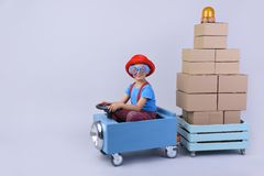 Smiling boy driving blue, fanny car. Smiling boy driving blue, fanny car and wagon with small boxes.Happy child with paper boxes on grey background. Studio shot stock images