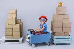 Smiling boy driving blue, fanny car. Smiling boy driving blue, fanny car and wagon with small boxes.Happy child with paper boxes on grey background. Studio shot royalty free stock photography