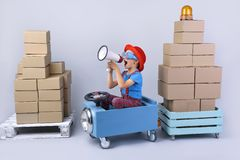 Smiling boy driving blue, fanny car. Smiling boy driving blue, fanny car and wagon with small boxes.Happy child with paper boxes on grey background. Studio shot royalty free stock image