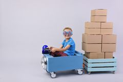 Smiling boy driving blue, fanny car. Smiling boy driving blue, fanny car and wagon with small boxes.Happy child with paper boxes on grey background. Studio shot stock photos