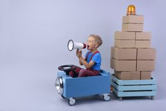 Smiling boy driving blue, fanny car. Smiling boy driving blue, fanny car and wagon with small boxes.Happy child with paper boxes on grey background. Studio shot royalty free stock images