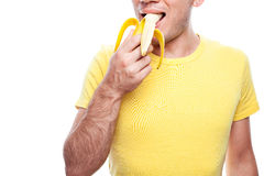 Smiling boy eating banana. Smiling handsome guy holding and biting (eating) yellow banana over white background. Healthcare concept. Copy-space. studio shot Royalty Free Stock Image