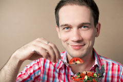 Smiling boy eating fresh vegan salad. Close-up portrait of a slim handsome boy eating salad over wooden background. studio shot Royalty Free Stock Photography
