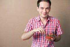 Smiling boy eating fresh vegan salad. Slim handsome boy eating salad over wooden background. studio shot Royalty Free Stock Images
