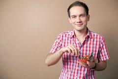 Smiling boy eating fresh vegan salad. Slim handsome boy eating salad over wooden background. studio shot Stock Photos
