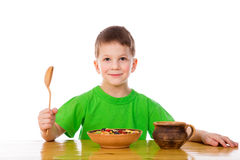 Smiling boy eating oatmeal at the table Royalty Free Stock Photography