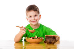 Smiling boy eating oatmeal at the table Stock Photo