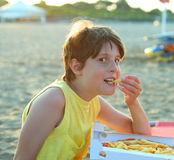 Smiling boy eats pizza with potato chips on the beach Stock Photography