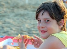 Smiling boy eats pizza with potato chips on the beach Royalty Free Stock Images