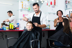 Smiling boy in elementary school age getting hairdo of man. Smiling boy in elementary school age getting hairdo of men hairdresser in beauty salon Royalty Free Stock Photo
