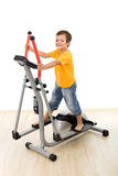 Smiling boy on elliptical trainer in the gym Royalty Free Stock Image