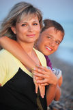 Smiling boy embraces young woman on beach Stock Photo