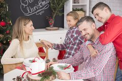 Smiling boy embracing happy father. Sitting at christmas table with wife and daughter Royalty Free Stock Images