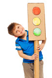 Smiling boy emerging from behind cardboard lights Royalty Free Stock Images