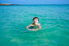 Smiling boy enjoys swimming in the sea. Young happy boy with brown hair enjoys swimming and playing in the beautiful sea stock images