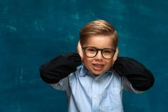 Smiling boy with eyeglasses on blue backdrop Royalty Free Stock Photo