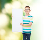 Smiling boy in eyeglasses with white blank board. Vision, health, advertisement, ecology and people concept - smiling little boy wearing eyeglasses with white stock photography