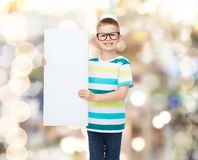 Smiling boy in eyeglasses with white blank board. Vision, health, advertisement, holidays and people concept - smiling little boy wearing eyeglasses with white stock photo