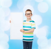 Smiling boy in eyeglasses with white blank board. Vision, health, advertisement and people concept - smiling little boy in eyeglasses with white blank board over royalty free stock image