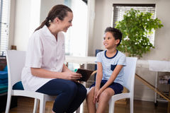 Smiling boy and female therapist sitting with digital tablet. At hospital ward Royalty Free Stock Image