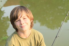 Smiling boy with fish-rod Stock Photos