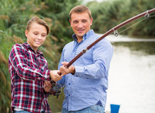 Smiling boy fishing with man on freshwater lake. Smiling boy fishing with men on freshwater lake on holiday Royalty Free Stock Photo