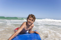 Smiling boy floating on body board in ocean Royalty Free Stock Image