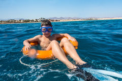 Smiling boy floating on lifebuoy in the sea. Smiling boy in swimming mask floating on lifebuoy in the sea Stock Images
