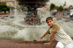 Smiling boy by fountain Royalty Free Stock Photos