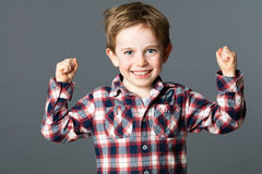 Smiling boy with freckles raising strong fists for tough health Royalty Free Stock Photos