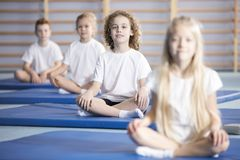 Friends during corrective gymnastics classes. Smiling boy and friends sitting on blue mats during a corrective gymnastics class royalty free stock image