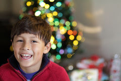 Smiling Boy in Front of Christmas Tree Stock Photo