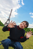 Smiling boy in front of the Eiffel Tower. Teenager laughing, playing and fooling around on the Champ de Mars in front of the Eiffel Tower (La Tour Eiffel) in Stock Images