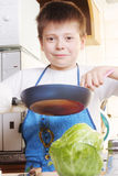 Smiling boy with frying-pan. Smiling boy in white shirt standing in kitchen with frying-pan Stock Photo