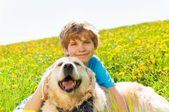 Smiling boy and funny dog sitting on grass Royalty Free Stock Image