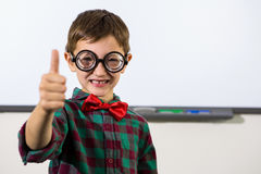 Smiling boy gesturing thumbs up sign. Portrait of smiling boy gesturing thumbs up sign in classroom Stock Photo