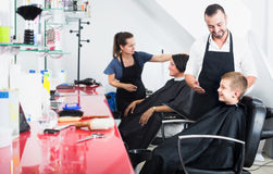 Smiling boy getting hairdo in crowded beauty salon Royalty Free Stock Photography