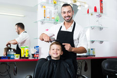 Smiling boy  getting hairstyle of man hairdresser Royalty Free Stock Images