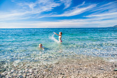 Smiling boy and girl on the beach, swim in the sea Stock Images