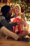 Smiling boy and girl exchanging Christmas presents royalty free stock image