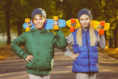 Smiling boy and girl holding color plastic penny. Boards or skateboards outdoor royalty free stock photography