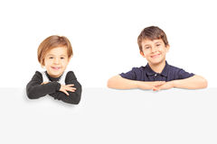 Smiling boy and girl posing behind a blank panel Stock Photography