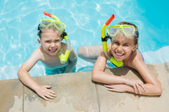 Smiling boy and girl relaxing on the side of swimming pool Royalty Free Stock Photo