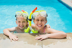 Smiling boy and girl relaxing on the side of swimming pool Stock Photo