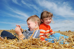 Smiling boy and girl in straw outdoors. Smiling Boy and girl sitting back-to-back on the straw outdoors over blue sky Stock Images